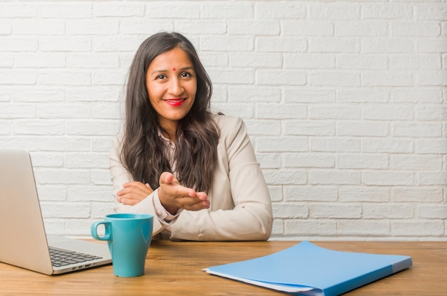 Young indian woman at the office reaching out to greet someone or gesturing to help