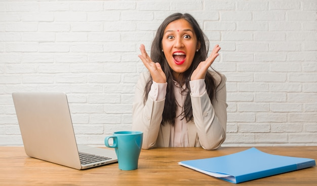 Young indian woman at the office surprised and shocked, looking with wide eyes
