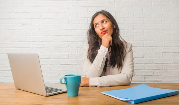 Young indian woman at the office thinking and looking up, confused about an idea