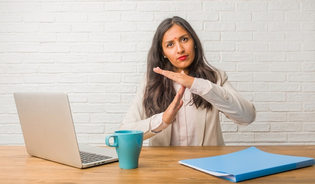 Young indian woman at the office tired and bored, making a timeout gesture