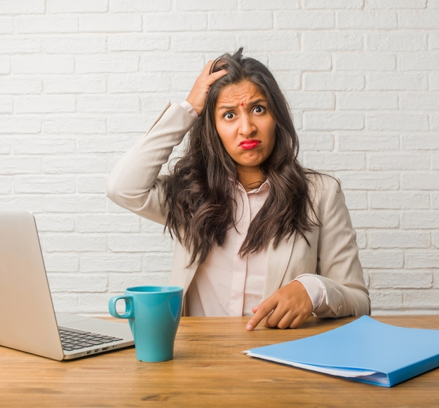 Young indian woman at the office worried and overwhelmed, forgetful, realize something