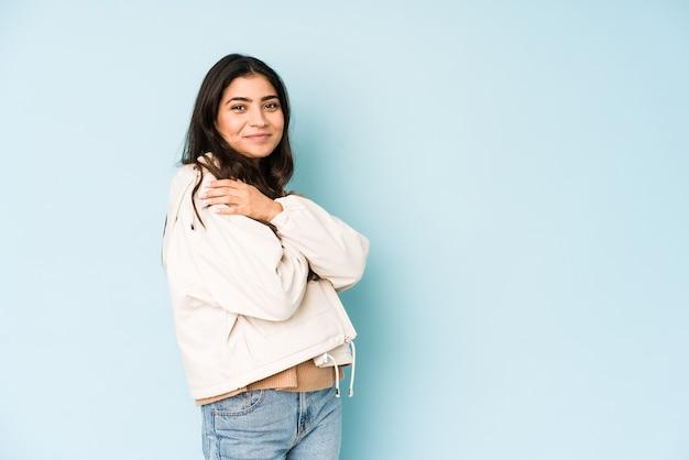 Молодая индийская женщина на голубых объятиях, беззаботно улыбается и счастлива.