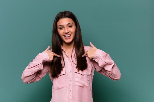 파란색에 젊은 인도 여자는 광범위 하 게 웃 고 손가락으로 가리키는 놀 랐 다.