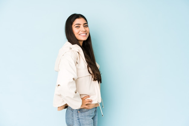 青い壁に若いインド人女性は腰に手を保つことに自信を持っています。