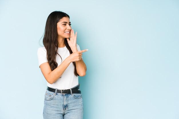 Молодая индийская женщина на синей стене говорит сплетню, указывая на сторону, сообщая что-то.