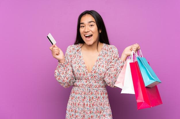 買い物袋とクレジットカードを保持している紫色の壁に若いインド人女性