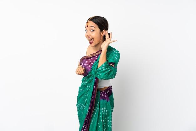 耳に手を置くことで何かを聞いて白い壁に若いインド人女性