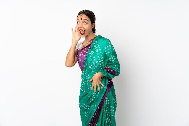 흰 벽에 젊은 인도 여자는 귀에 손을 넣어 뭔가를 듣고