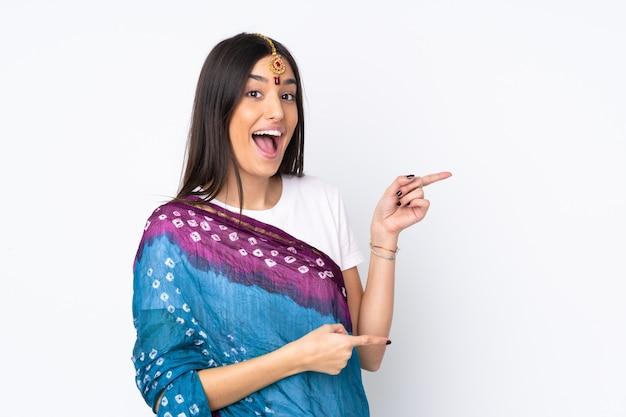 Молодая индийская женщина на белой стене удивлен и указывая стороны