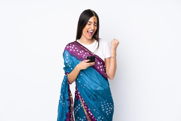 Молодая индийская женщина на белой стене с телефоном в положении победы