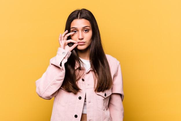 秘密を保持している唇に指で黄色の若いインド人女性。