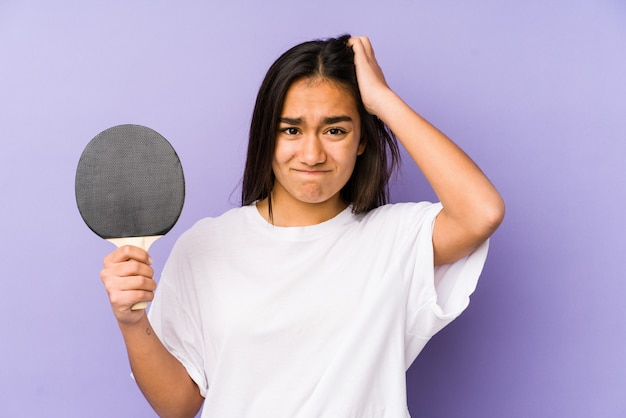 Young indian woman playing ping pong being shocked, she has remembered important meeting.