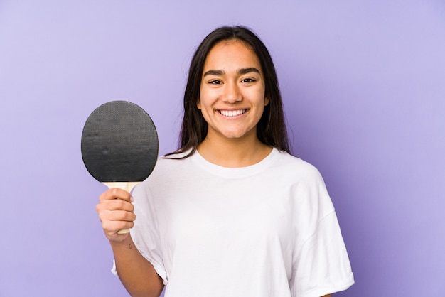 Young indian woman playing ping pong happy, smiling and cheerful.