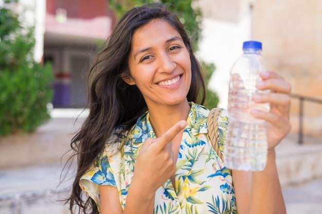 거리에서 물 한 병을 가리키는 젊은 인도 여성