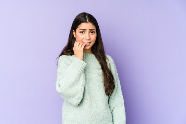 Young indian woman on purple wall biting fingernails, nervous and very anxious.