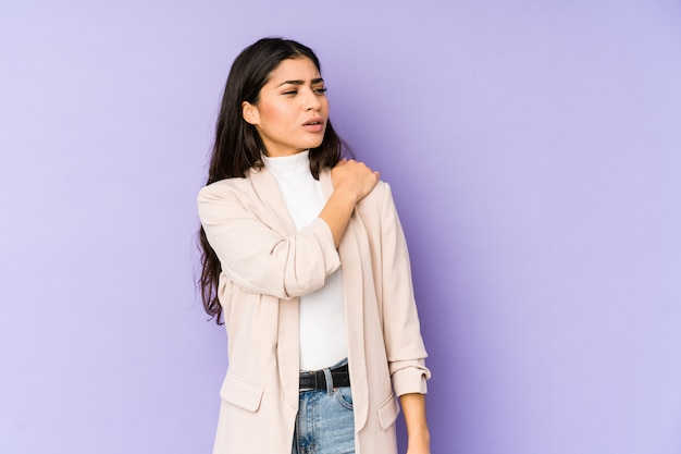 Young indian woman on purple wall having a shoulder pain.