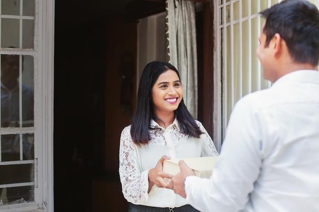 配達パッケージを受け取る若いインドの女性