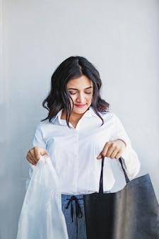 플라스틱과 재사용 가능한 가방 사이에서 선택하는 젊은 인도 여성