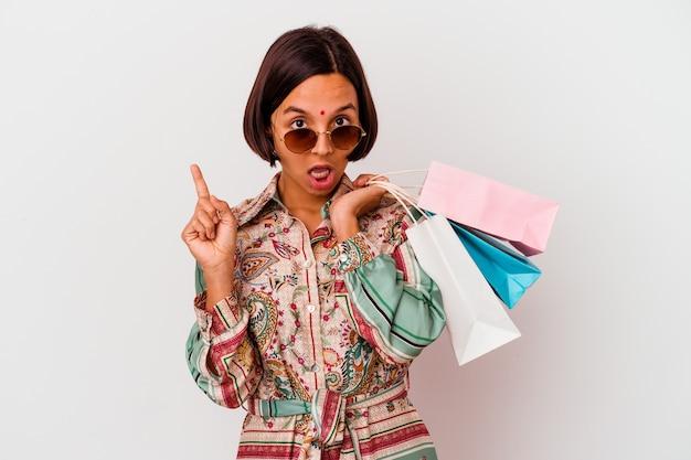 Молодая индийская женщина, делающая покупки в одежде, изолированной на белом фоне, имеет отличную идею, концепцию творчества.