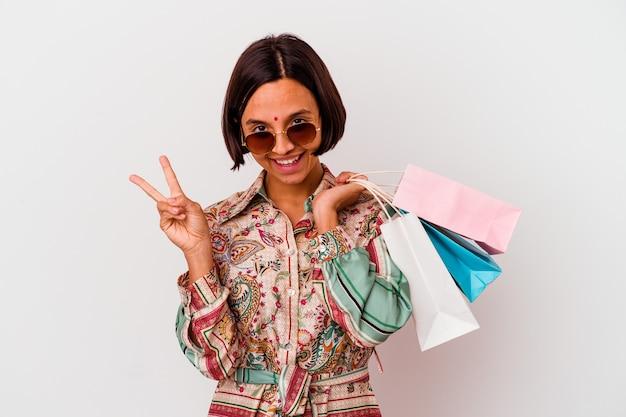 Молодая индийская женщина, покупающая одежду на белом фоне, радостная и беззаботная, показывая пальцами символ мира.