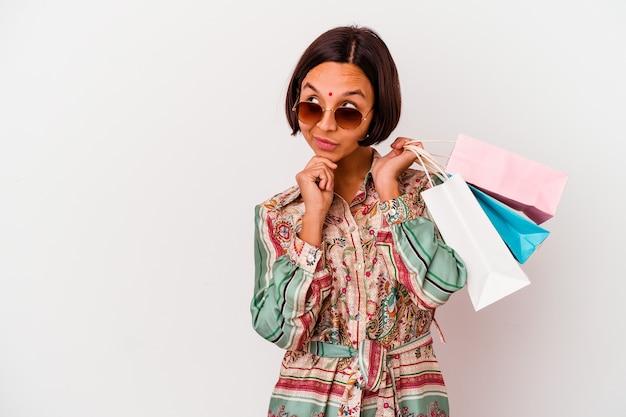 Молодая индийская женщина, делающая покупки в одежде, изолированной на белом фоне, смотрит в сторону с сомнительным и скептическим выражением лица.