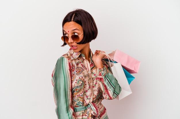 Молодая индийская женщина, делающая покупки в одежде, изолированной на белом фоне, смотрит в сторону улыбается, весела и приятно.