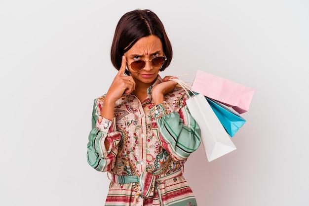 Молодая индийская женщина, делающая покупки одежду, изолированная на белом фоне, указывая храм пальцем, думая, сосредоточилась на задаче.