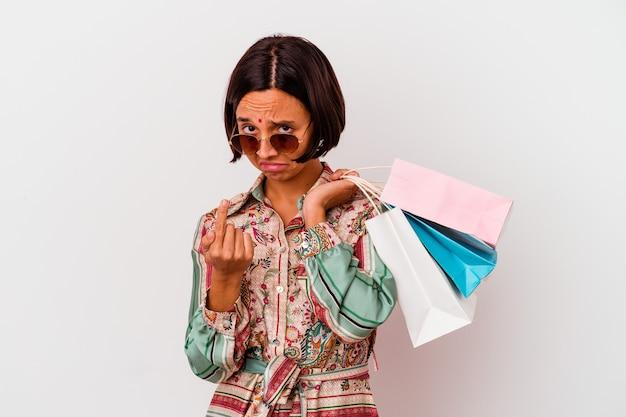 Молодая индийская женщина делает покупки в одежде, изолированной на белом фоне, указывая пальцем на вас, как будто приглашая подойти ближе.