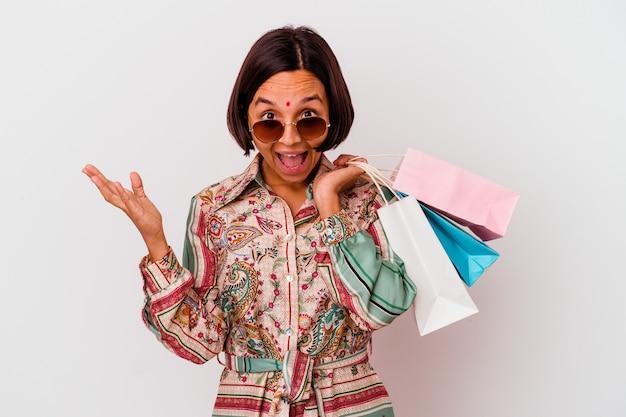 Молодая индийская женщина, делающая покупки одежды, изолированные на белом фоне, получая приятный сюрприз, возбужденная и поднимающая руки.