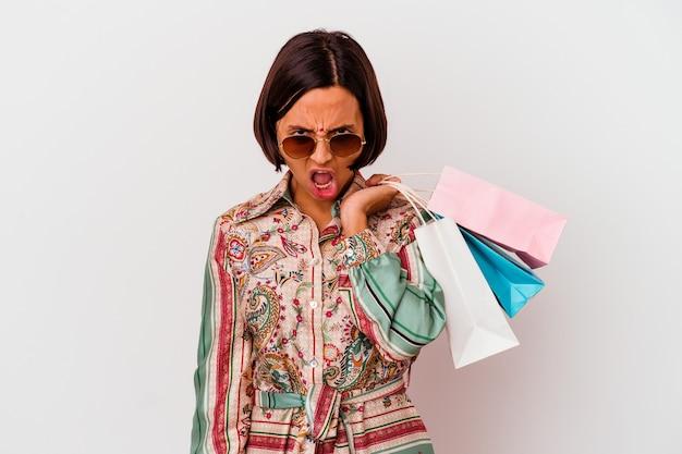 Молодая индийская женщина, делающая покупки одежду, изолированная на белом фоне, кричала очень сердито и агрессивно.