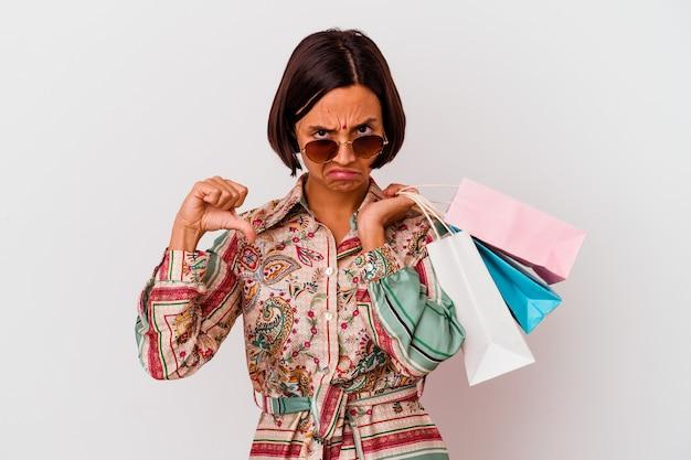 Молодая индийская женщина делает покупки в одежде, изолированной на белом фоне, показывая жест неприязни, пальцы вниз. концепция несогласия.