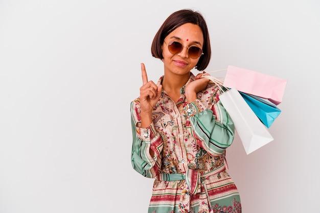 Молодая индийская женщина покупает одежду, изолированную на белом фоне, показывая номер один пальцем.