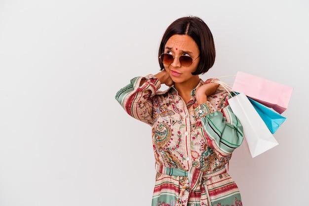 Молодая индийская женщина, делающая покупки в одежде, изолированной на белом фоне, касаясь затылка, думая и делая выбор.