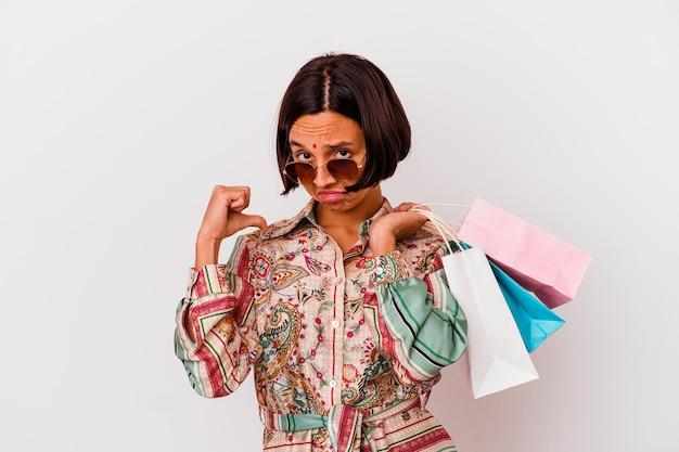 Молодая индийская женщина делает покупки в одежде, изолированной на белом, чувствует гордость и уверенность в себе, пример для подражания.