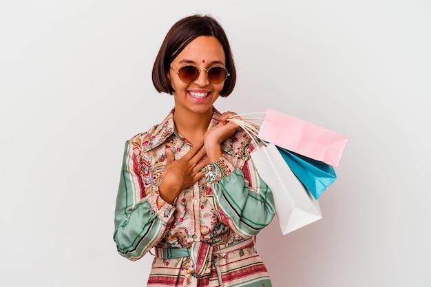 Молодая индийская женщина делает покупки в одежде, изолированной на белом, громко смеется, держа руку на груди.