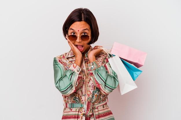 Молодая индийская женщина, делающая покупки в одежде, изолированной на белом, удивлена и шокирована.
