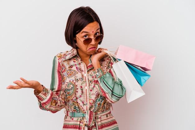Молодая индийская женщина, делающая покупки какой-то одежды, изолированной на белой стене, пожимает плечами и смущенно открывает глаза.