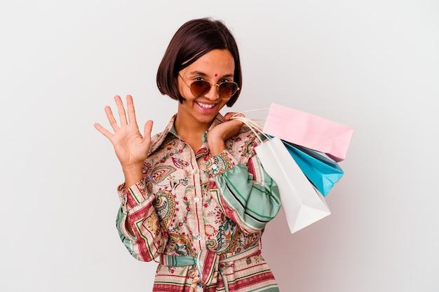 Молодая индийская женщина покупает одежду, изолированную на белой стене, улыбается веселый, показывая номер пять пальцами.