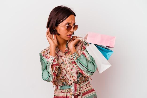 Молодая индийская женщина делает покупки в одежде, изолированной на белой стене, пытается слушать сплетни.