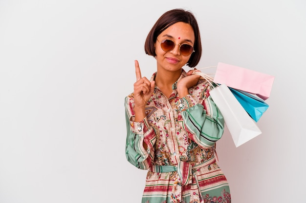 Young indian woman shopping some clothes isolated on white background showing number one with finger.