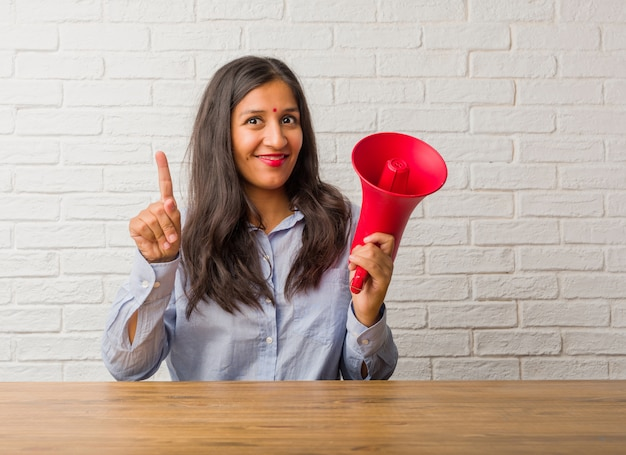 Young indian woman showing number one, symbol of counting, concept of mathematics, confident and cheerful. holding a megaphone.