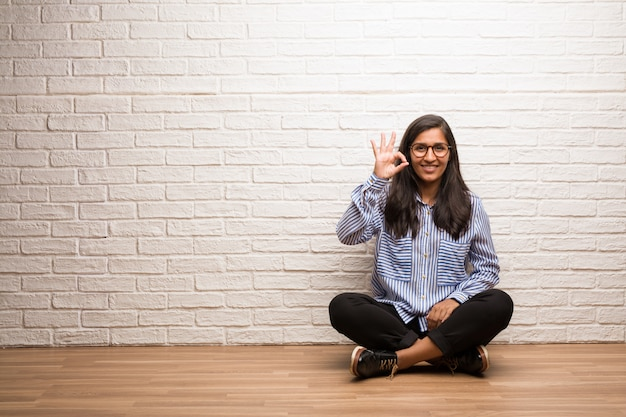 Young indian woman sit against a brick wall cheerful and confident doing ok gesture