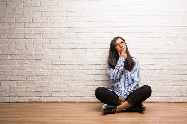 Young indian woman sit against a brick wall doubting and confused, thinking of an idea or worried about something