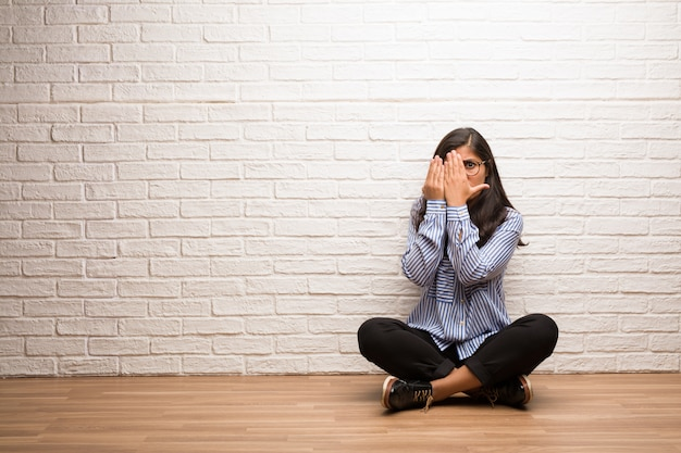 Young indian woman sit against a brick wall feels worried and scared, looking and covering