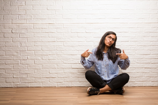 Young indian woman sit against a brick wall proud and confident, pointing fingers