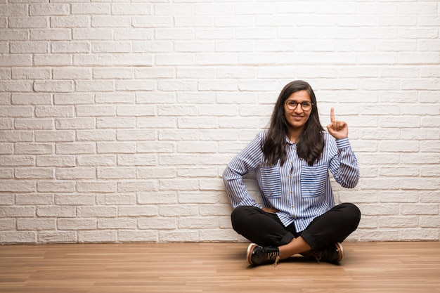 Young indian woman sit against a brick wall showing number one, symbol of counting, concept of mathematics, confident and cheerful