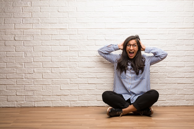 Young indian woman sit against a brick wall surprised and shocked, looking with wide eyes.
