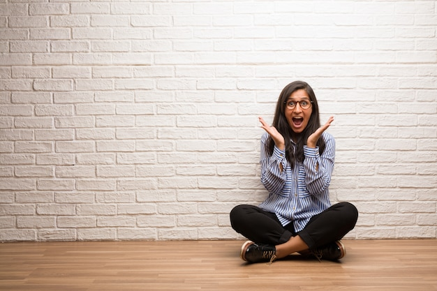 Young indian woman sit against a brick wall surprised and shocked, looking with wide eyes