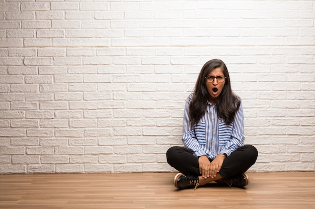 Young indian woman sit against a brick wall very angry and upset, very tense, screaming fu