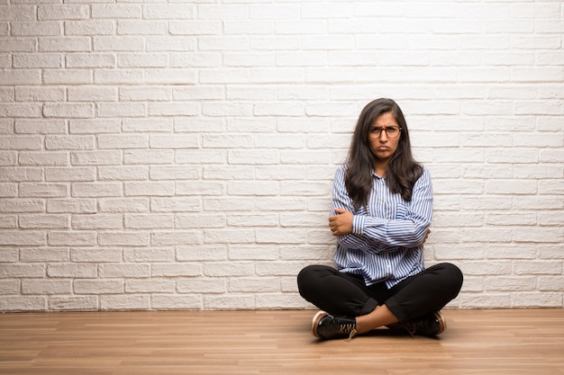 Young indian woman sit against a brick wall very angry and upset, very tense, screaming furious, negative and crazy